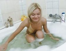 yellow-haired Russian rubbing the button in a bath tube