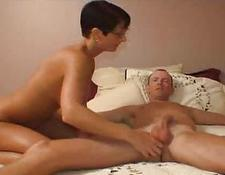 attractive brunette in black glasses undresses on soft bed and fucks stud