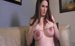 Pregnant brunette does a striptease and poses nude on the couch