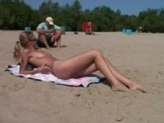 Naked teenie nudist lets the water kiss her .